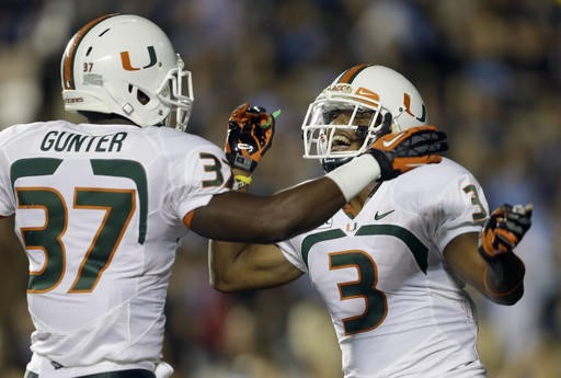 Miami's Ladarius Gunter (37) and Tracy Howard (3)celebrate Howard's interception against North Carolina during the first half of an NCAA college...