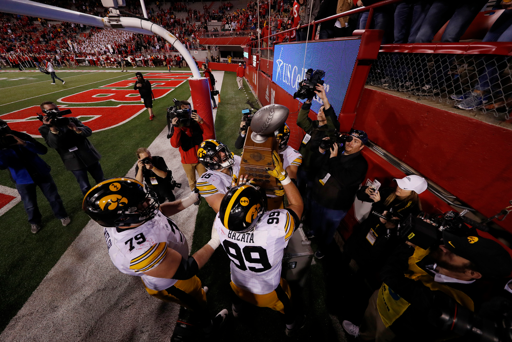 Iowa Hawkeyes offensive lineman Sean Welsh (79), defensive lineman Nathan Bazata (99), and fullback Drake Kulick (45)