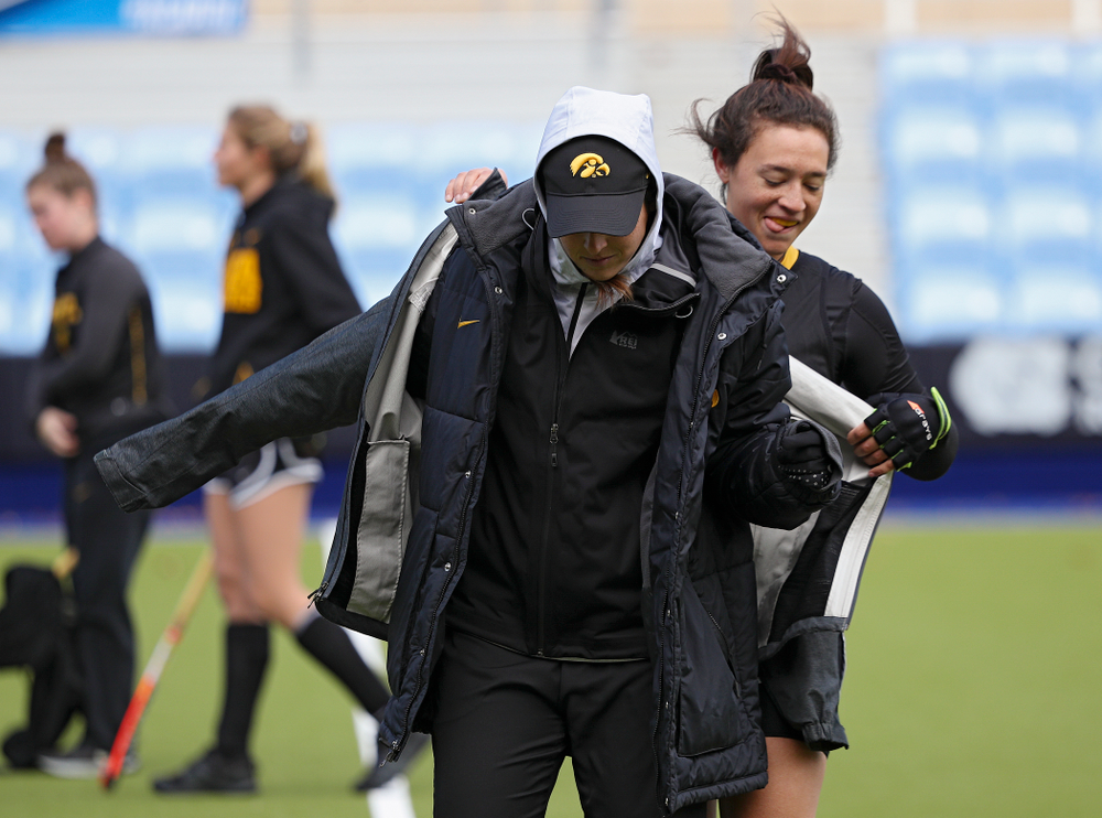 Iowa's Mya Christopher (18) puts another coat on Ashley Renteria, strength coach, during their practice at Karen Shelton Stadium in Chapel Hill, N.C. on Saturday, Nov 16, 2019. (Stephen Mally/hawkeyesports.com)