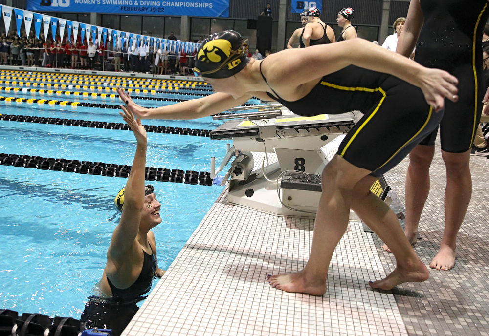 Iowa's Hannah Burvill gets a high five after setting a school record in the women's 400 yard medley relay event during the 2020 Women's Big Ten Swimming and Diving Championships at the Campus Recreation and Wellness Center in Iowa City on Thursday, February 20, 2020. (Stephen Mally/hawkeyesports.com)