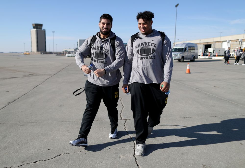 Iowa Hawkeyes defensive end A.J. Epenesa (94) and offensive lineman Tristan Wirfs (74) board the team plane at the Eastern Iowa Airport Saturday, December 21, 2019 on the way to San Diego, CA for the Holiday Bowl. (Brian Ray/hawkeyesports.com)