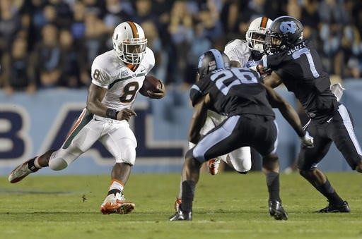 Miami's Duke Johnson (8) runs the ball as North Carolina's Dominique Green (26) and Tim Scott (7) move in to attempt the tackle during the first half...