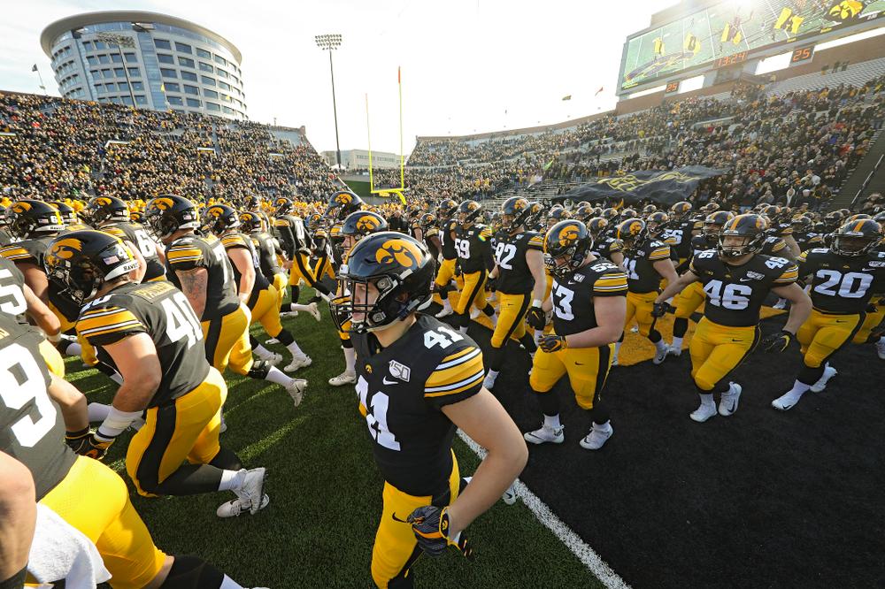 The Iowa Hawkeyes swarm as they take the field before their game at Kinnick Stadium in Iowa City on Saturday, Nov 23, 2019. (Stephen Mally/hawkeyesports.com)