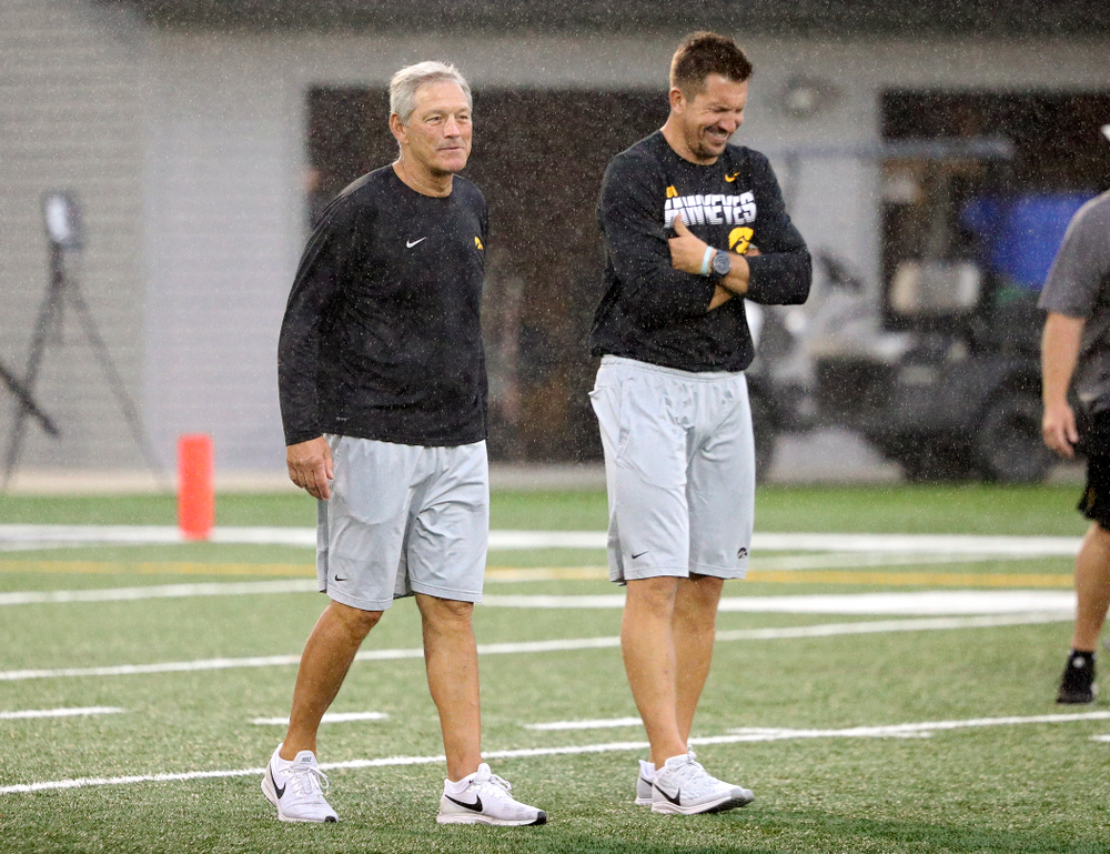 Iowa Hawkeyes head coach Kirk Ferentz talks with former Iowa Hawkeyes and Indianapolis Colts tight end Dallas Clark as rain falls durning Fall Camp Practice No. 17 at the Hansen Football Performance Center in Iowa City on Wednesday, Aug 21, 2019. (Stephen Mally/hawkeyesports.com)