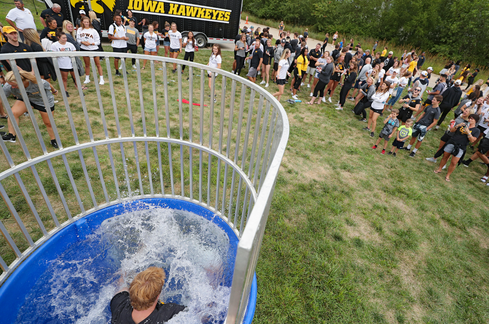 Iowa Women's Tennis program coordinator Daniel Leitner drops into the water in the dunk tank during the Student-Athlete Kickoff outside the Karro Athletics Hall of Fame Building in Iowa City on Sunday, Aug 25, 2019. (Stephen Mally/hawkeyesports.com)