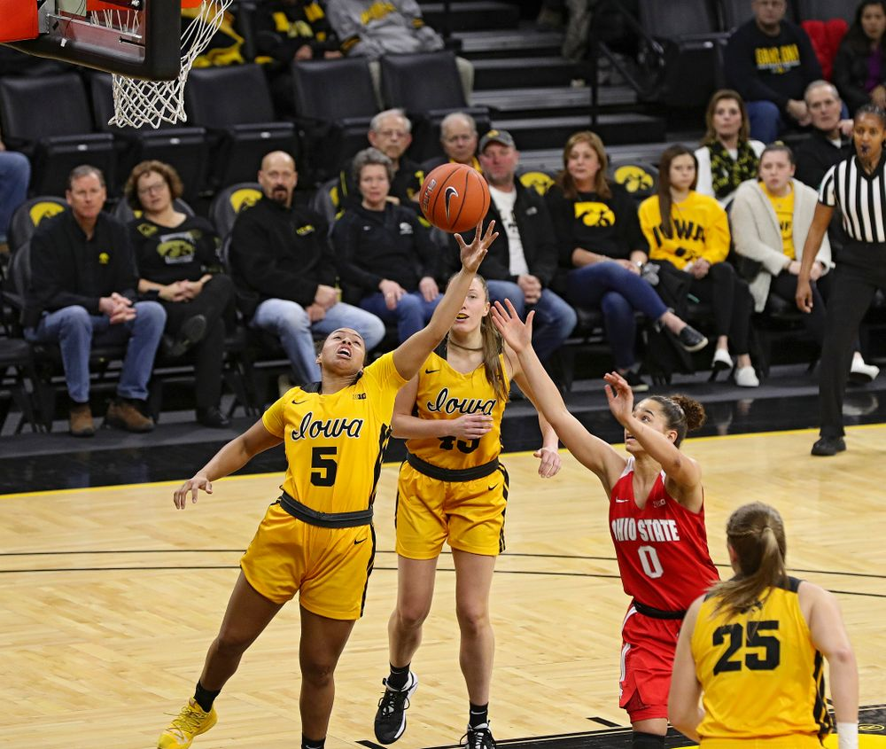 Iowa Hawkeyes guard Alexis Sevillian (5) pulls in a rebound as forward Amanda Ollinger (43) looks on during the first quarter of their game at Carver-Hawkeye Arena in Iowa City on Thursday, January 23, 2020. (Stephen Mally/hawkeyesports.com)