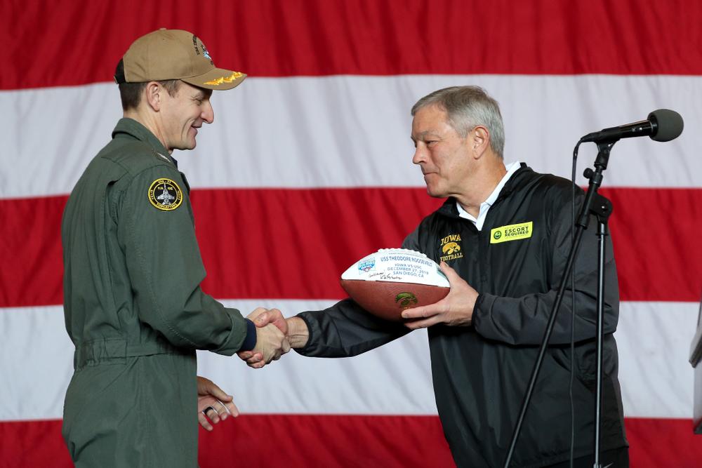 Iowa Hawkeyes head coach Kirk Ferentz presents a ball to Captain Brett Crozier during a tour of the USS Theodore Roosevelt (CVN-71) Tuesday, December 24, 2019 at the Naval Base Coronado. (Brian Ray/hawkeyesports.com)