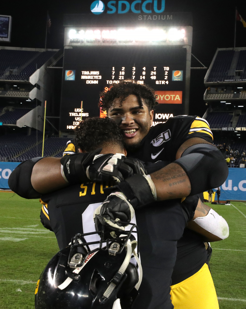 Iowa Hawkeyes offensive lineman Tristan Wirfs (74) hugs defensive back Geno Stone (9) after their win against USC in the Holiday Bowl Friday, December 27, 2019 at San Diego Community Credit Union Stadium.  (Brian Ray/hawkeyesports.com)