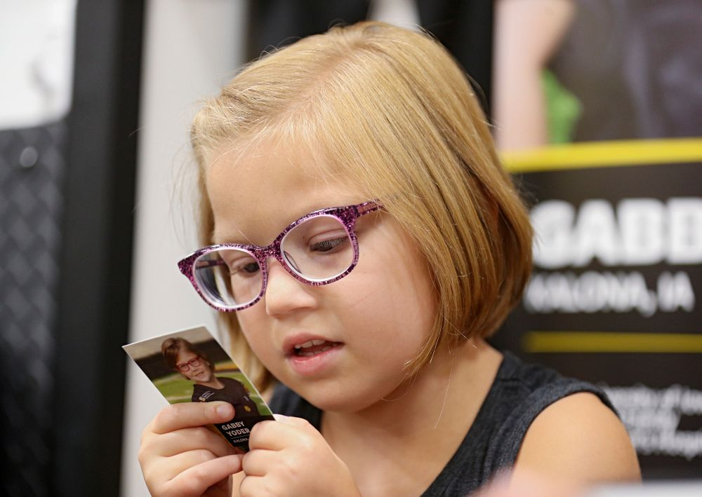 Kid Captain Gabby Yoder reads the back of her trading card during Kids Day at Kinnick Stadium in Iowa City on Saturday, Aug 10, 2019. (Stephen Mally/hawkeyesports.com)
