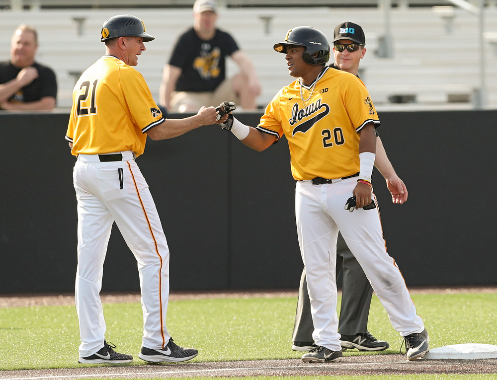 Iowa Hawkeyes head coach Rick Heller greets first baseman Izaya Fullard (20) on third base during the third inning of their game against Northern Illinois at Duane Banks Field in Iowa City on Tuesday, Apr. 16, 2019. (Stephen Mally/hawkeyesports.com)