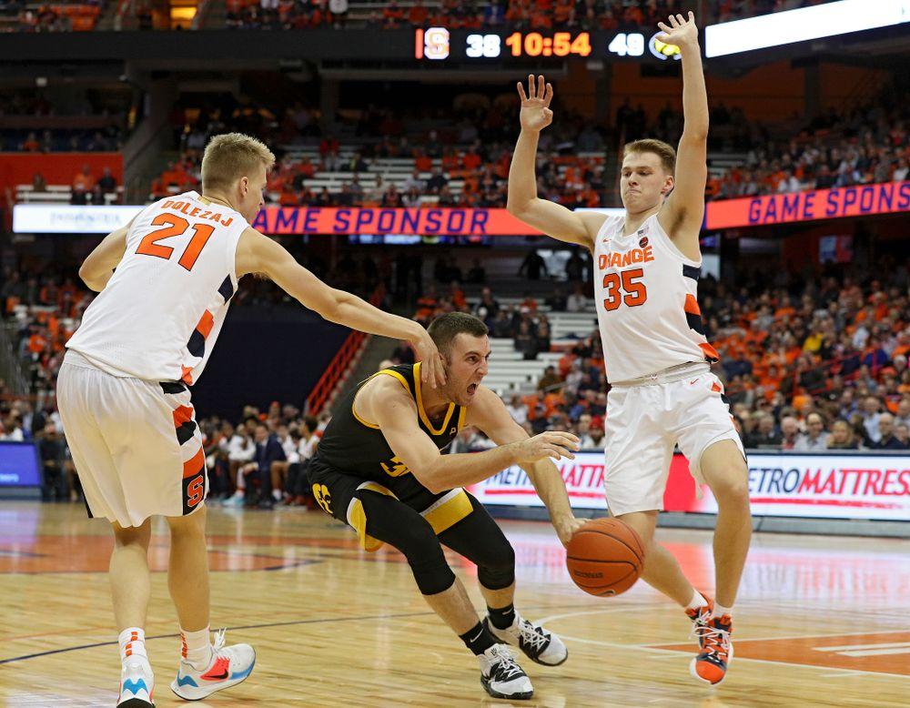 Iowa Hawkeyes guard Connor McCaffery (30) passes the ball between two defenders during the second half of their ACC/Big Ten Challenge game at the Carrier Dome in Syracuse, N.Y. on Tuesday, Dec 3, 2019. (Stephen Mally/hawkeyesports.com)