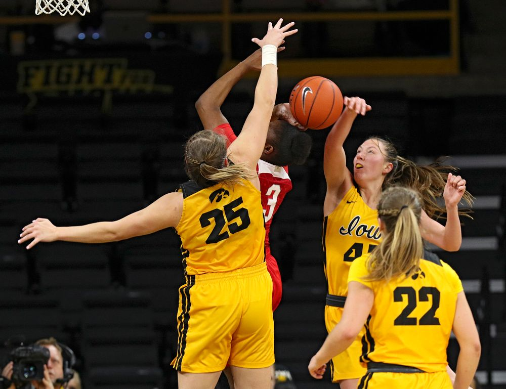 Iowa Hawkeyes forward Amanda Ollinger (43) blocks a shot by Ohio State Buckeyes guard Janai Crooms (3) as forward Monika Czinano (25) defends during the third quarter of their game at Carver-Hawkeye Arena in Iowa City on Thursday, January 23, 2020. (Stephen Mally/hawkeyesports.com)