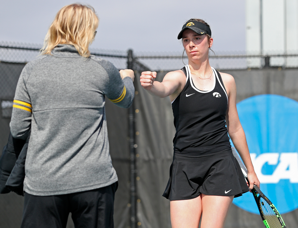 Iowa head coach Sasha Schmid (from left) fist bumps Samantha Mannix during a match against Rutgers at the Hawkeye Tennis and Recreation Complex in Iowa City on Friday, Apr. 5, 2019. (Stephen Mally/hawkeyesports.com)