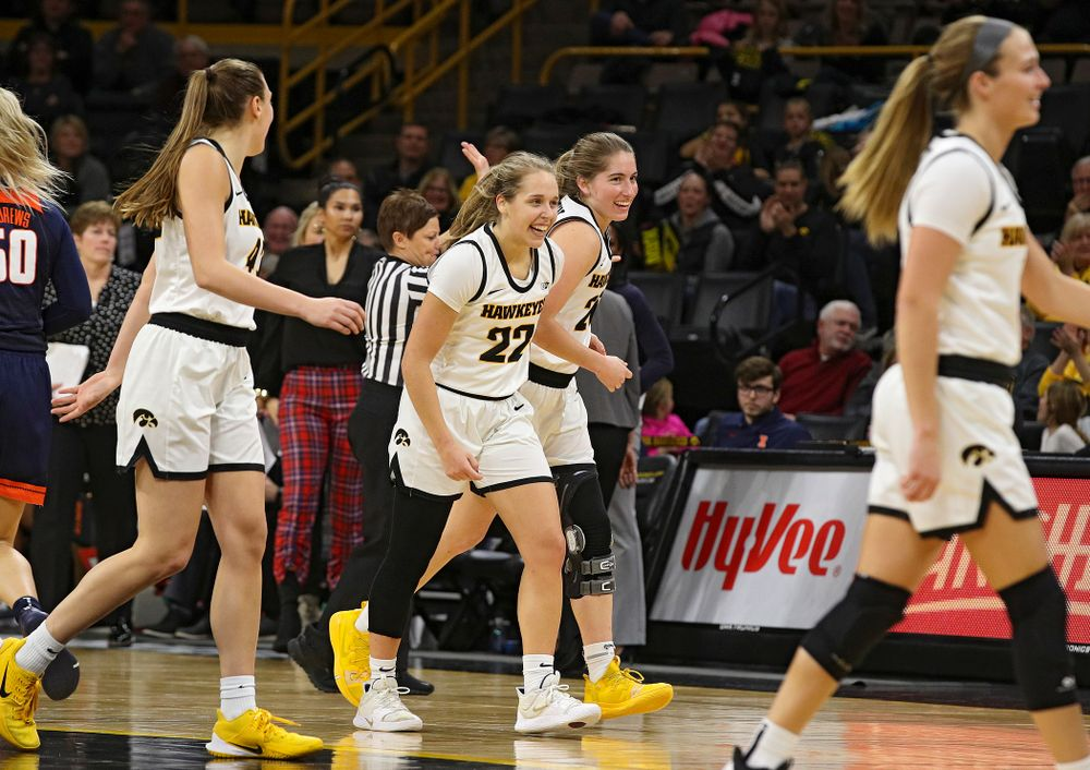 Iowa Hawkeyes guard Kathleen Doyle (22) and guard Kate Martin (20) are all smiles as they head back to their bench during a timeout in the fourth quarter of their game at Carver-Hawkeye Arena in Iowa City on Tuesday, December 31, 2019. (Stephen Mally/hawkeyesports.com)