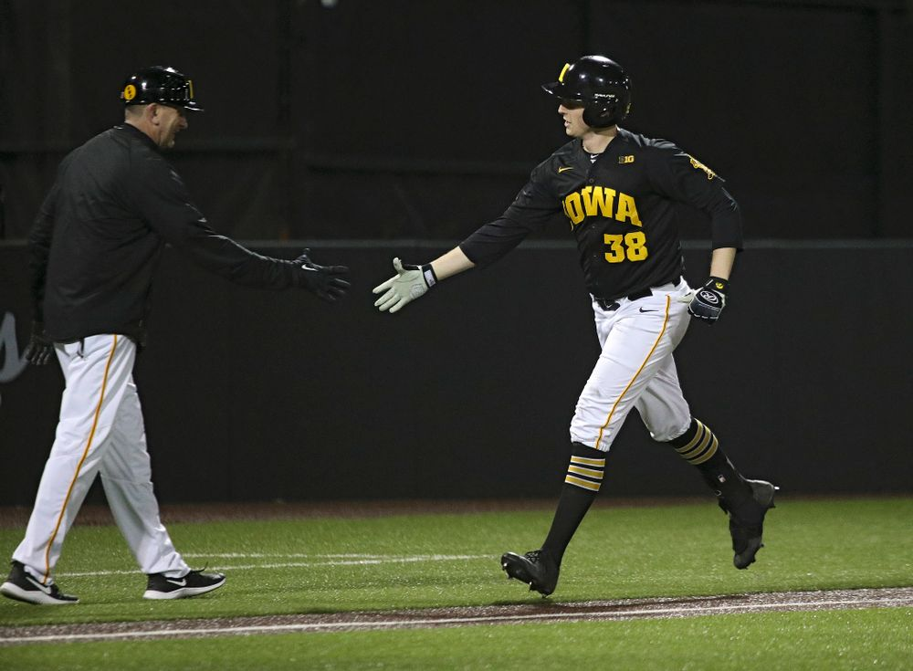 Iowa Hawkeyes head coach Rick Heller greets designated hitter Trenton Wallace (38) as he rounds the bases after hitting a home run during the eighth inning of their game at Duane Banks Field in Iowa City on Tuesday, March 3, 2020. (Stephen Mally/hawkeyesports.com)
