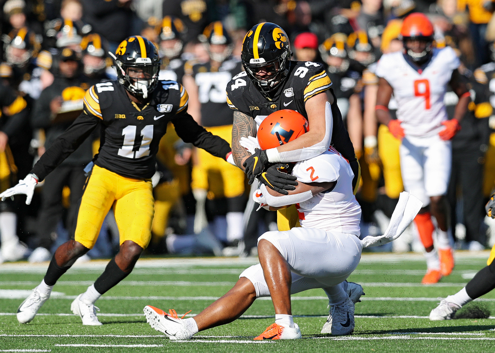 Iowa Hawkeyes defensive end A.J. Epenesa (94) wraps up Illinois Fighting Illini running back Reggie Corbin (2) during the first quarter of their game at Kinnick Stadium in Iowa City on Saturday, Nov 23, 2019. (Stephen Mally/hawkeyesports.com)