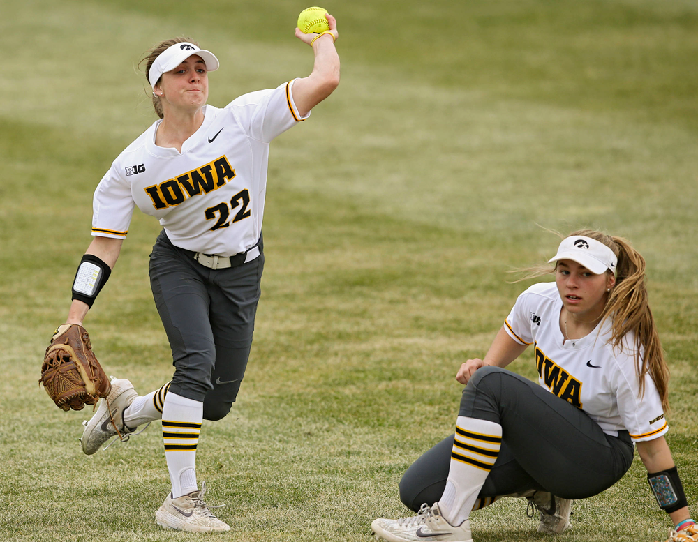 Iowa Hawkeyes Hallie Ketcham (22) throws the ball as Sydney Owens (5) looks on during the second inning of their Big Ten Conference softball game at Pearl Field in Iowa City on Friday, Mar. 29, 2019. (Stephen Mally/hawkeyesports.com)