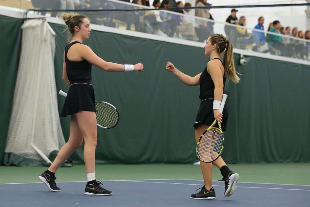 Iowa's Samantha Mannix and Danielle Burich bump fists during doubles during the Iowa women's tennis meet vs UNI  on Saturday, February 29, 2020 at the Hawkeye Tennis and Recreation Complex. (Lily Smith/hawkeyesports.com)