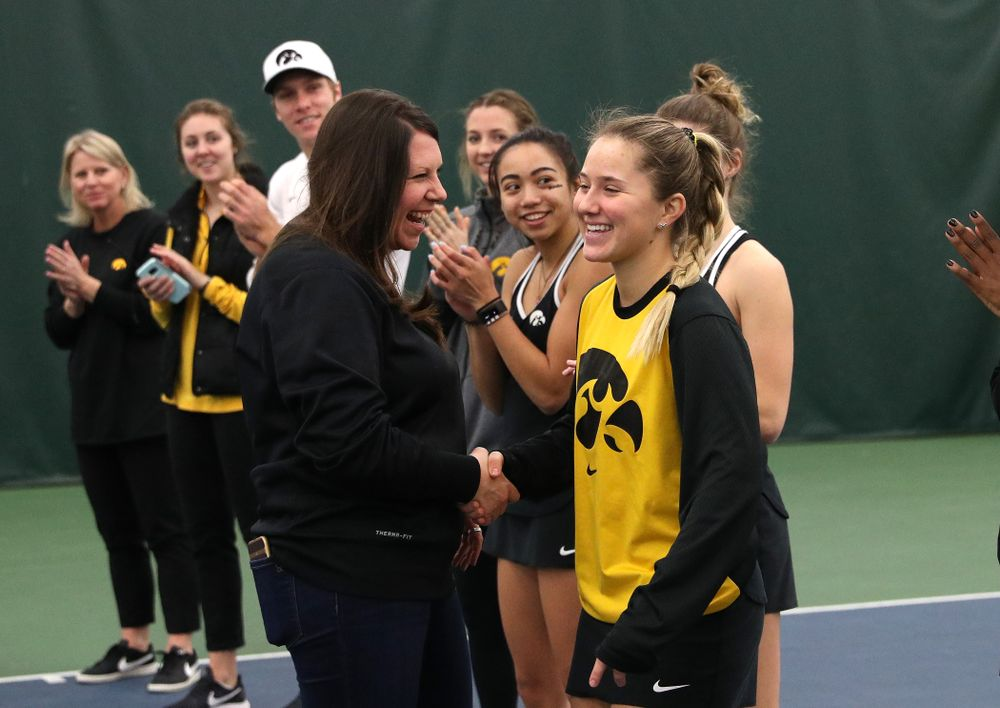 Academic Student Services Associate Director Kara Park congratulates Danielle Burich for earning a 3.0 GPA or better during the fall semester before their match against the Penn State Nittany Lions Sunday, February 24, 2019 at the Hawkeye Tennis and Recreation Complex. (Brian Ray/hawkeyesports.com)