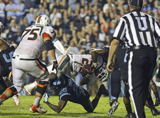Miami's Dallas Crawford (25) dives into the end zone for the winning touchdown as North Carolina's Dominique Green (26) tries to make the stop during...