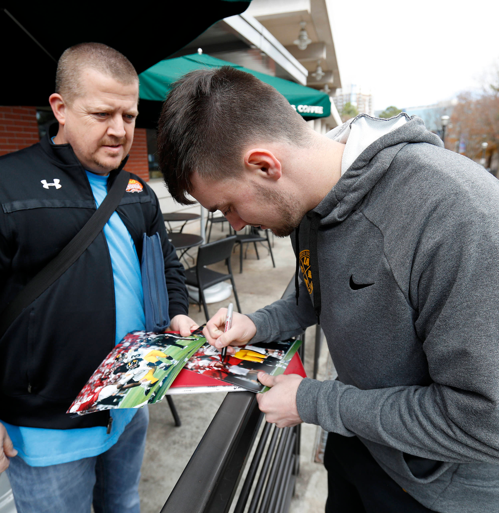Keith Duncan autographing photos of the game-winning field goal at Nebraska