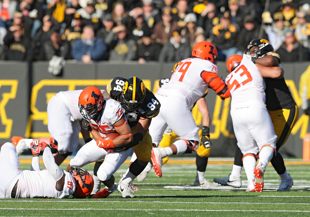 Iowa Hawkeyes defensive end A.J. Epenesa (94) brings down Illinois Fighting Illini running back Dre Brown (25) during the third quarter of their game at Kinnick Stadium in Iowa City on Saturday, Nov 23, 2019. (Stephen Mally/hawkeyesports.com)