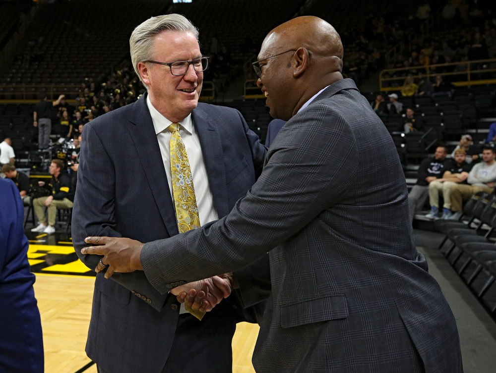 Iowa Hawkeyes head coach Fran McCaffery (from left) shakes hand with Cal Poly Mustangs head coach John Smith before their game at Carver-Hawkeye Arena in Iowa City on Sunday, Nov 24, 2019. (Stephen Mally/hawkeyesports.com)