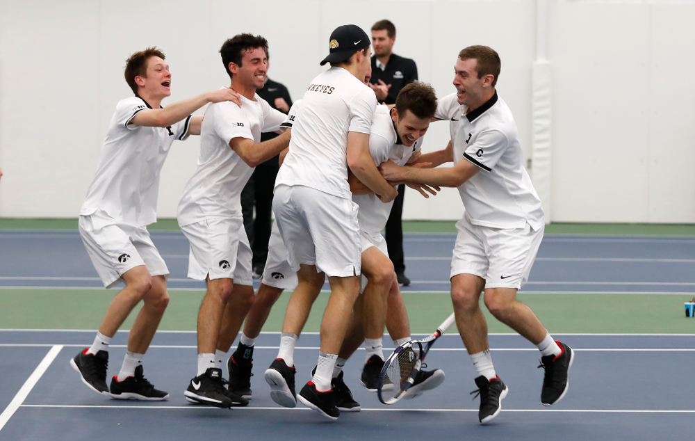 Iowa's Piotr Smietana celebrates with his teammates after clinching the match against Purdue Sunday, April 15, 2018 at the Hawkeye Tennis an