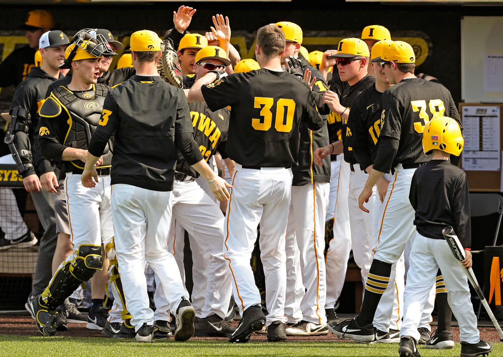 Iowa Hawkeyes right fielder Connor McCaffery (30) is greeted by teammates after scoring a run during the fourth inning of their game against Rutgers at Duane Banks Field in Iowa City on Saturday, Apr. 6, 2019. (Stephen Mally/hawkeyesports.com)
