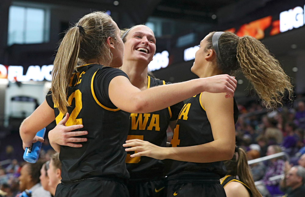 Iowa Hawkeyes guard Kathleen Doyle (22), guard Makenzie Meyer (3), and guard Gabbie Marshall (24) celebrate after guard Megan Meyer (not pictured) made a 3-pointer during the fourth quarter of their game at Welsh-Ryan Arena in Evanston, Ill. on Sunday, January 5, 2020. (Stephen Mally/hawkeyesports.com)