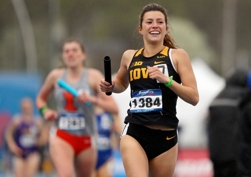 Iowa's Taylor Arco smiles as crosses the finish line while running the women's sprint medley relay event during the third day of the Drake Relays at Drake Stadium in Des Moines on Saturday, Apr. 27, 2019. (Stephen Mally/hawkeyesports.com)