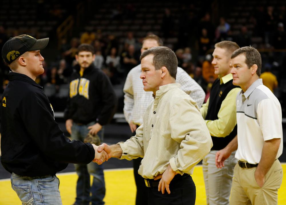 Iowa senior Phillip Laux shakes hands with associate head coach Terry Brands  following their meet against Northwestern