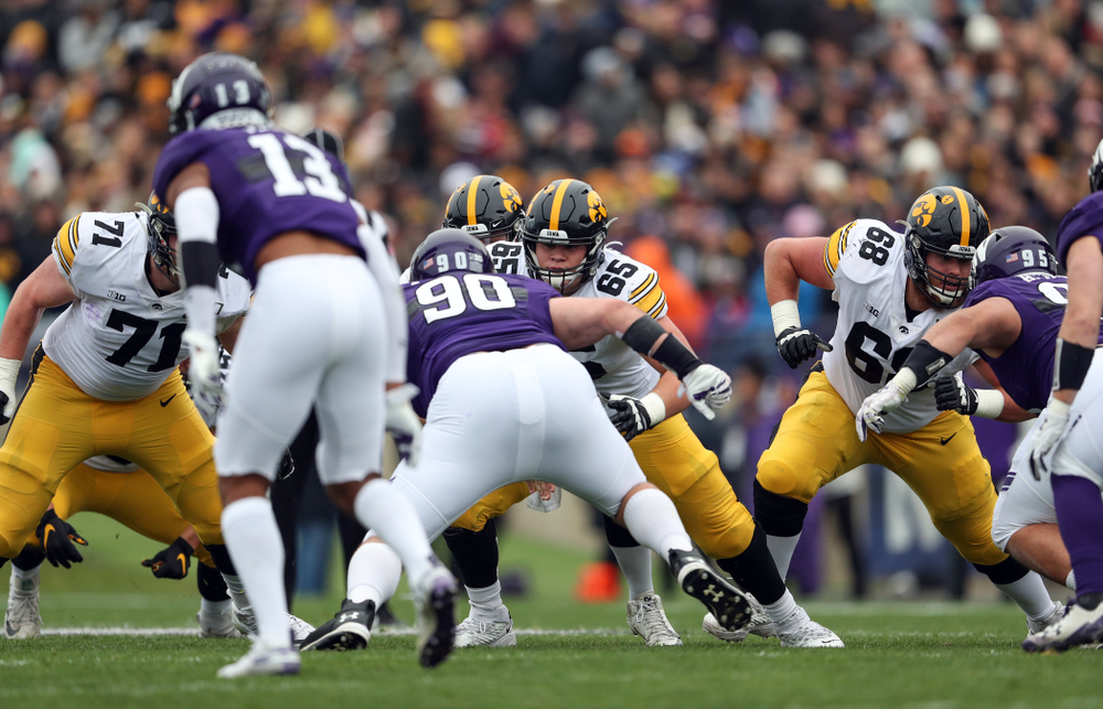 Iowa Hawkeyes offensive lineman Mark Kallenberger (71), offensive lineman Tyler Linderbaum (65), and offensive lineman Landan Paulsen (68) against the Northwestern Wildcats Saturday, October 26, 2019 at Ryan Field in Evanston, Ill. (Brian Ray/hawkeyesports.com)