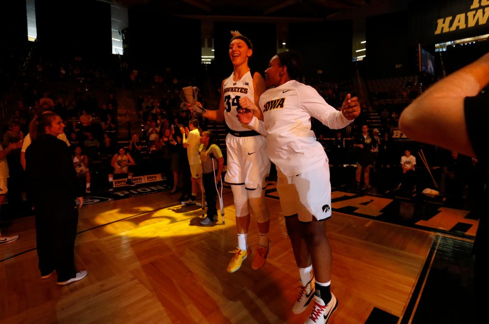 Iowa Hawkeyes forward Carly Mohns (34) and guard Zion Sanders (24)