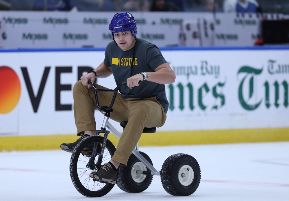 Iowa Hawkeyes quarterback Nate Stanley (4) rides a tricycle during a contest against Mississippi State during the first intermission of the Tampa Bay Lightning game Thursday, December 27, 2018 at Amalie Arena. (Brian Ray/hawkeyesports.com)