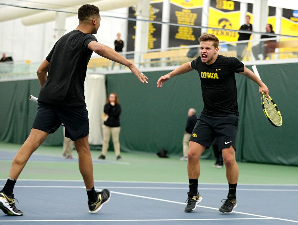 Iowa's Oliver Okonkwo (from left) and Will Davies celebrate a point during their doubles match at the Hawkeye Tennis and Recreation Complex in Iowa City on Friday, February 14, 2020. (Stephen Mally/hawkeyesports.com)