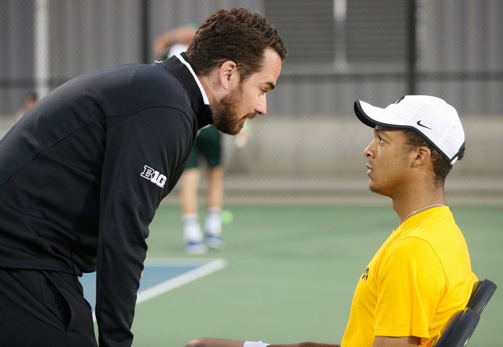 Iowa head coach Ross Wilson (from left) talks with Oliver Okonkwo during his match again Michigan State at the Hawkeye Tennis and Recreation Complex in Iowa City on Friday, Apr. 19, 2019. (Stephen Mally/hawkeyesports.com)