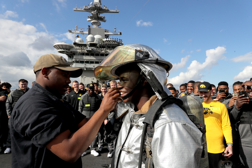 Iowa Hawkeyes running back Keontae Luckett (20) puts on a firefighting suit during a tour of the USS Theodore Roosevelt (CVN-71) Tuesday, December 24, 2019 at the Naval Base Coronado. (Brian Ray/hawkeyesports.com)