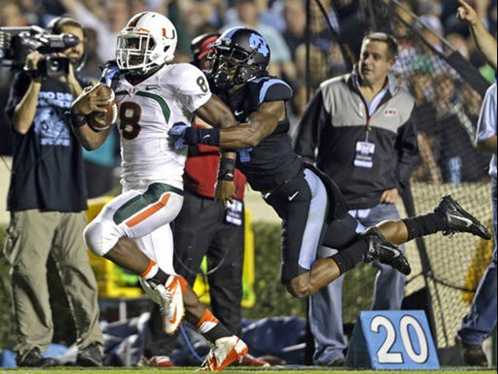 Miami's Duke Johnson (8) runs the ball as North Carolina's Brian Walker reaches for the tackle during the first half of an NCAA college football game...