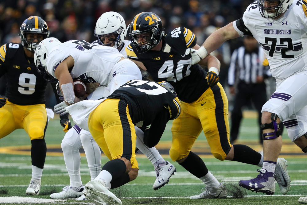 Iowa Hawkeyes defensive back Amani Hooker (27) and Iowa Hawkeyes defensive end Parker Hesse (40) make a tackle during a game against Northwestern at Kinnick Stadium on November 10, 2018. (Tork Mason/hawkeyesports.com)
