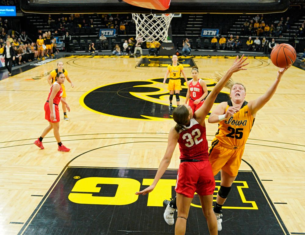 Iowa Hawkeyes forward Monika Czinano (25) scores a basket around Ohio State Buckeyes forward Aaliyah Patty (32) during the first quarter of their game at Carver-Hawkeye Arena in Iowa City on Thursday, January 23, 2020. (Stephen Mally/hawkeyesports.com)