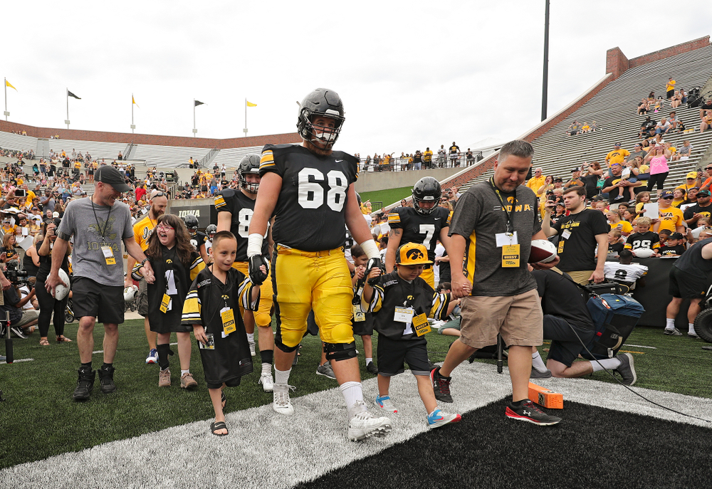 Kid Captains Lucy Roth, Skylar Hardee, and Jeg Weets lead the others as they swarm with Iowa Hawkeyes offensive lineman Landan Paulsen (68) during Kids Day at Kinnick Stadium in Iowa City on Saturday, Aug 10, 2019. (Stephen Mally/hawkeyesports.com)