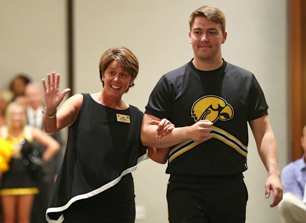 2019 University of Iowa Athletics Hall of Fame inductee Deb Brickey walks to her seat with a Spirit Squad member during the Hall of Fame Induction Ceremony at the Coralville Marriott Hotel and Conference Center in Coralville on Friday, Aug 30, 2019. (Stephen Mally/hawkeyesports.com)