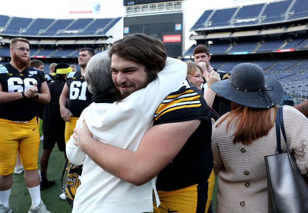 Iowa Hawkeyes offensive lineman Kyler Schott (64) hugs family members following the team photo Wednesday, December 25, 2019 at SDCCU Stadium in San Diego. (Brian Ray/hawkeyesports.com)