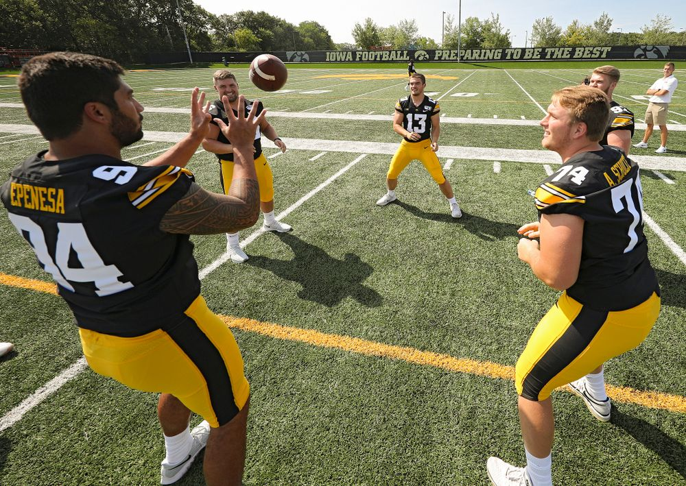 Iowa Hawkeyes defensive end A.J. Epenesa (94), defensive lineman Dalles Jacobus (66), linebacker Joe Evans (13), defensive lineman Austin Schulte (74), and defensive lineman John Waggoner (92) play around with a ball during Iowa Football Media Day at the Hansen Football Performance Center in Iowa City on Friday, Aug 9, 2019. (Stephen Mally/hawkeyesports.com)