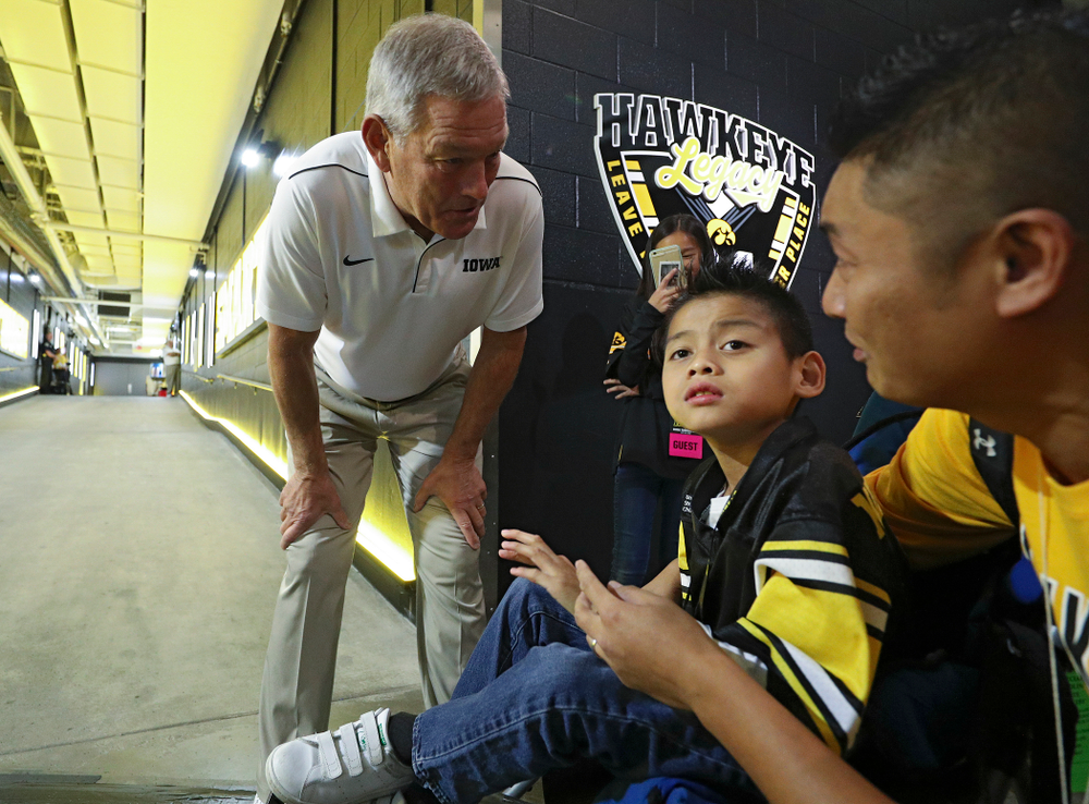 Iowa Hawkeyes head coach Kirk Ferentz talks with Kid Captain Enzo Thongsoum before their game at Kinnick Stadium in Iowa City on Saturday, Sep 28, 2019. (Stephen Mally/hawkeyesports.com)