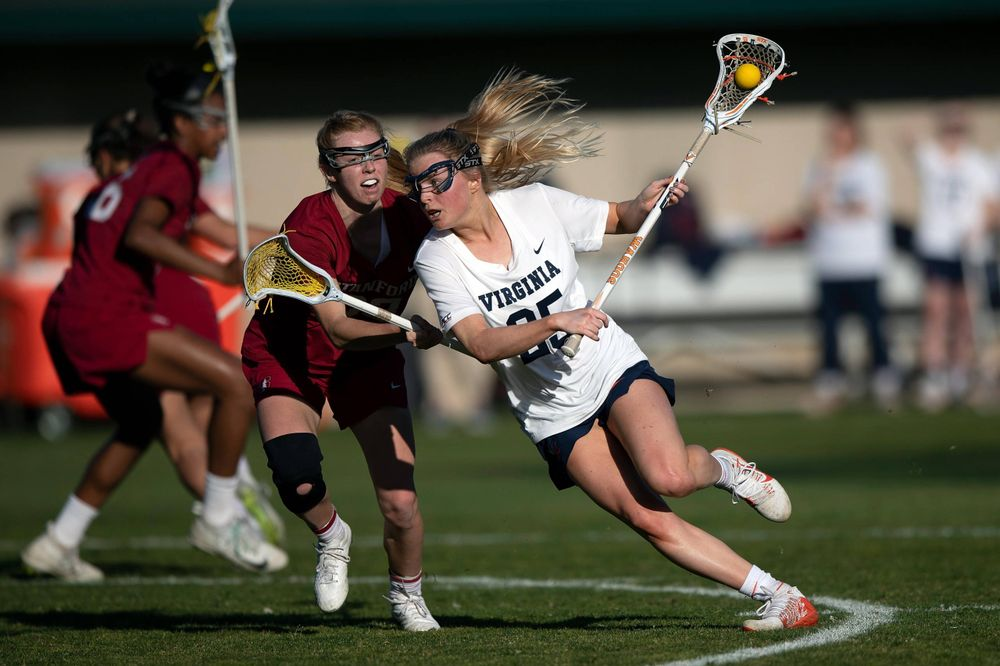 STANFORD, California - FEBRUARY 14:  Virginia Cavaliers midfield Courtlynne Caskin (25) is defended by Stanford Cardinal attack Kelleigh Keating (23) during the first half at Cagan Stadium on February 14, 2020 in Stanford, California. The Virginia Cavaliers defeated the Stanford Cardinal 12-11. (Photo by Jason O. Watson)