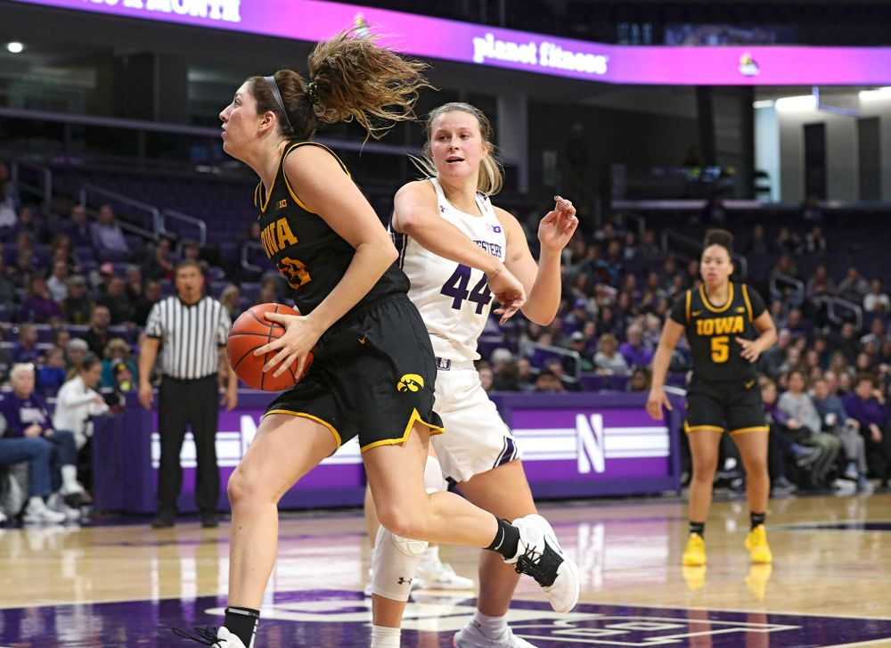 Iowa Hawkeyes guard Mckenna Warnock (14) spins away from Northwestern Wildcats forward Abi Scheid (44) before scoring a basket during the fourth quarter of their game at Welsh-Ryan Arena in Evanston, Ill. on Sunday, January 5, 2020. (Stephen Mally/hawkeyesports.com)