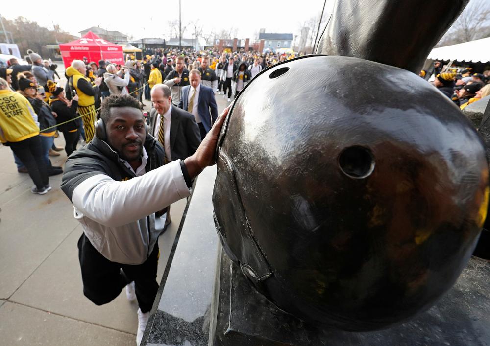 Iowa Hawkeyes linebacker Amani Jones (52) touches the helmet on the Nile Kinnick statue before their game at Kinnick Stadium in Iowa City on Saturday, Nov 23, 2019. (Stephen Mally/hawkeyesports.com)