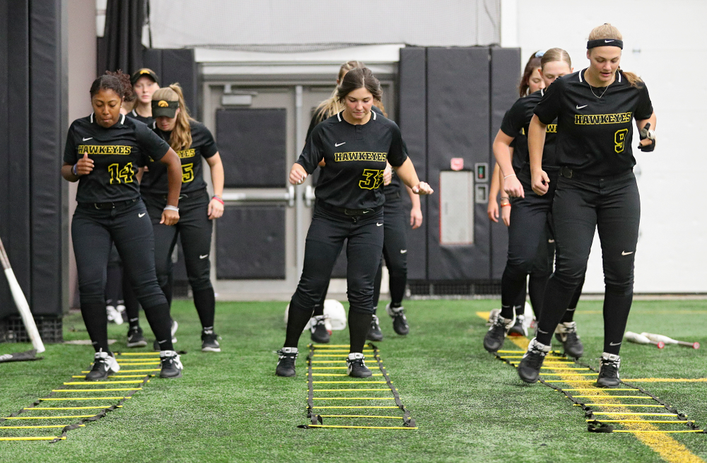 Iowa infielder Nia Carter (14), outfielder Riley Sheehy (33), and utility/catcher Abby Lien (9) run a drill during Iowa Softball Media Day at the Hawkeye Tennis and Recreation Complex in Iowa City on Thursday, January 30, 2020. (Stephen Mally/hawkeyesports.com)